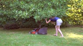 Barefeet girl woman working in garden cutting grass with lawn mower. 4K