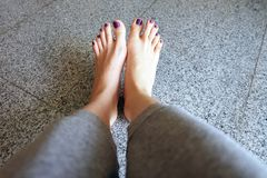 Barefeet with Nail Pedicure. Close Up Woman Legs Wear Gray Pants Standing On Gray Tile Background Royalty Free Stock Photos