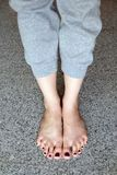 Barefeet with Nail Pedicure. Close Up Woman Legs Wear Gray Pants Standing On Gray Tile Background. Great for Any Use Royalty Free Stock Photography