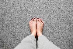 Barefeet with Nail Pedicure. Close Up Woman Legs Wear Gray Pants Standing On Gray Tile Background Royalty Free Stock Images