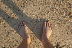 Barefeet in sand. On beach in summer holidays relaxing Stock Photo