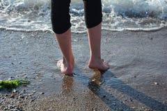 Feet before a wave on the sandy beach royalty free stock photos