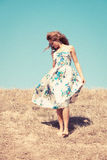 Barefoot. Young woman barefoot in silk dress on top of the hill  sky in background, retro colours, grain added Royalty Free Stock Photography