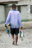 Barefoot African black fisherman diver carries a caught fish Royalty Free Stock Image