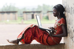 Barefoot African Model Working On Her Laptop Computer Business S. Ymbol. Education for Africa: Technology Symbol African Woman Studying Learning Lesson Stock Photos