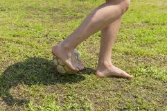 Barefoot amateur soccer player on old and bad field. With shabby ball stock image