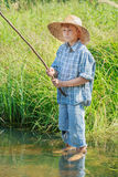 Barefoot angler boy fishing standing in transparent freshwater pond Royalty Free Stock Photo
