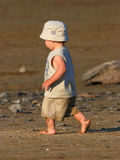 Barefoot Baby. Barefoot child dressed in matching beige shorts, t shirt and hat, walking purposefully along a sandy beach in the summer royalty free stock images