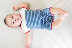 Barefoot baby boy in a striped dress lies. On white bedsheet royalty free stock photo