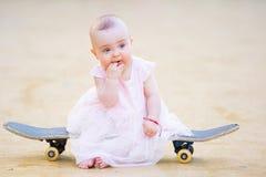 Barefoot baby girl on skateboard Stock Photo