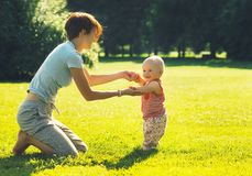 Baby`s first steps. Mother and child in nature stock photo
