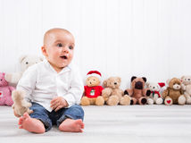 Barefoot baby on white background with cuddly toys - cute little Stock Photo