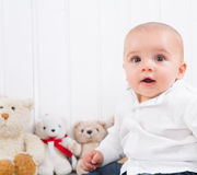 Barefoot baby on white background with cuddly toys - cute little Stock Images