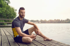 Barefoot bearded young man relaxing on a deck Stock Image