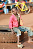 Barefoot black boy, resting, sitting on car tire. Makuyuni, Arusha, Tanzania - February 13, 2008: Unknown African barefoot black boy in pink jacket, about 10 stock photography