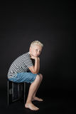 Barefoot blond boy wearing stripped shirt stares. At camera while sitting on keyboard box Stock Image