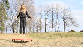 Barefoot blond girl jumping on trampoline. Blond girl - barefoot hairy kid in black clothes jumping on black and red kids´ small trampoline standing on grass stock footage