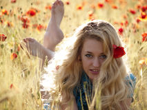 Barefoot blonde in poppies. Beautiful Barefoot blonde lady laying in poppy field Stock Photo