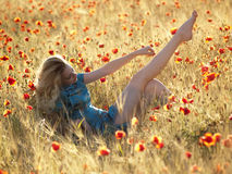 Barefoot blonde in poppies. Beautiful Barefoot blonde lady laying in poppy field Stock Photos
