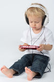 Barefoot boy in blue jeans with headphones playing Stock Photo