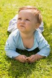 Barefoot boy crawling on the grass.  Stock Image