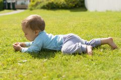 Barefoot boy crawling on the grass.  Royalty Free Stock Photo