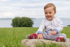 Barefoot boy crawling on the grass Stock Photo
