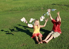 Barefoot boy and girl throwing money. Barefoot boy and girl throwing lots of money royalty free stock photo