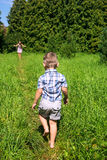 Barefoot boy goes to mother on track among high grass Stock Images