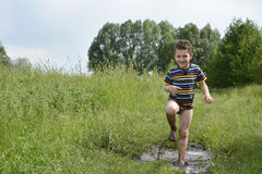Barefoot boy runs through a puddle. Royalty Free Stock Images