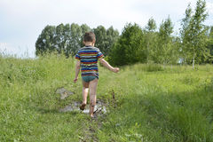 Barefoot boy runs through a puddle. Royalty Free Stock Image