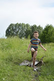 Barefoot boy runs through a puddle. Stock Image