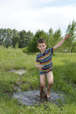 Barefoot boy runs through a puddle. Stock Photos