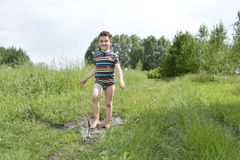 Barefoot boy runs through a puddle. Royalty Free Stock Photo
