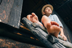 Barefoot boy sits on barn ladder Stock Photography