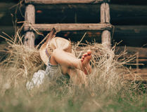 Barefoot boy sleeps on the grass near ladder in haystack Stock Photos