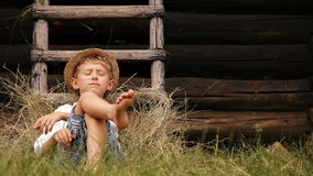Barefoot boy sleeps on the grass near ladder in haystack stock video footage