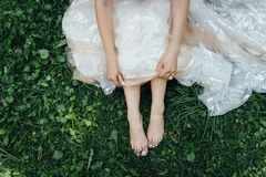 Barefoot bride on grass in summer time. Wedding day stock photos