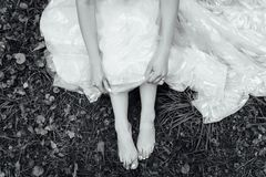 Barefoot bride on grass in summer time. Wedding day. Black and white photo stock photos
