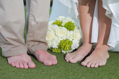 Barefoot bride and groom. Legs of barefoot bride and groom with bouquet of flowers royalty free stock images