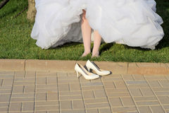 Barefoot Bride and Her Shoes Royalty Free Stock Image