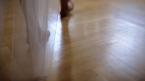 Barefoot bride in a white wedding dress going on the floor of her room. stock footage