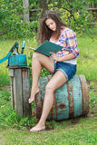 Barefoot brunette girl sitting on old vintage blue wooden barrel with book Royalty Free Stock Photo