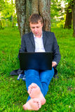 Barefoot businessman with a computer Royalty Free Stock Photography
