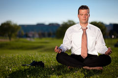 Barefoot businessman meditating Stock Photo