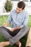 Barefoot businessman sitting and writing on paper with pencil Stock Photos