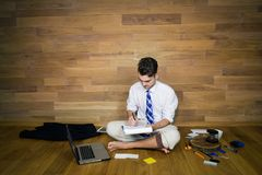 A barefoot businessman after working day sits on the floor. Against a wall and thinking about business solution. Young man working at home in funny clothes Royalty Free Stock Photos