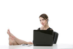 Barefoot businesswoman relaxing at her desk Royalty Free Stock Image