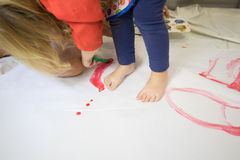 Barefoot child painting white paper with red watercolor Royalty Free Stock Photo