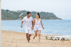 Barefoot couple on sand seashore in cloudy day Stock Images